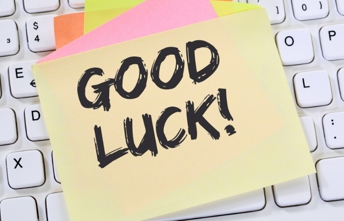 """a post it note stuck to a keyboard that reads """"Good luck!"""""""
