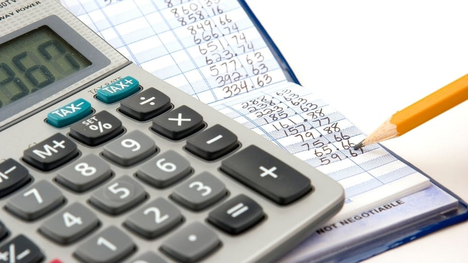 A picture of a calculator next to a checkbook to represent balancing a checkbook