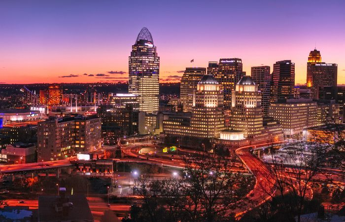a photo of the Cincinnati skyline at dusk showing all the city lights from buildings and vehicles