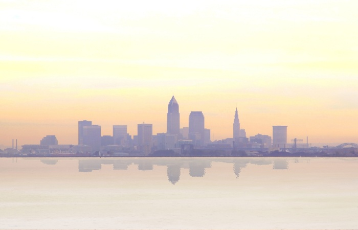 a hazy photo of the city of Cleveland from a distance across a large body of water