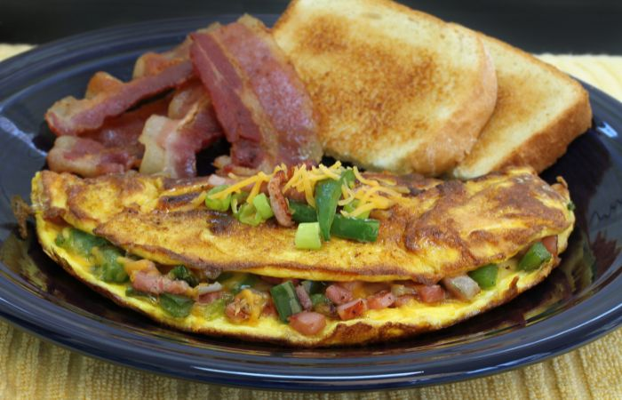 a photo of Denver omelette with a side of bacon and toast