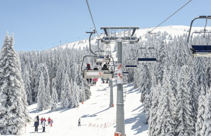 a picture of three people sitting on a chair lift on a snowy mountain in Denver Colorado