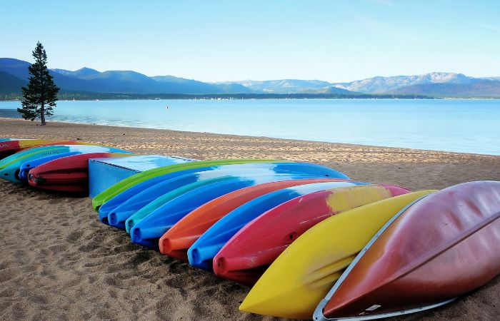 a picture of a bunch of colorful kayaks on the sandy shore of Lake Taho
