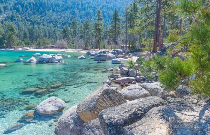 a beautiful scenic photo of lake tahoe, the rocks, and the trees surrounding the lake