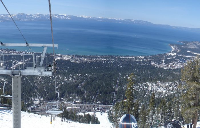 a photo looking down over the snow covered Lake Tahoe area, showing the sky hills and chair lift