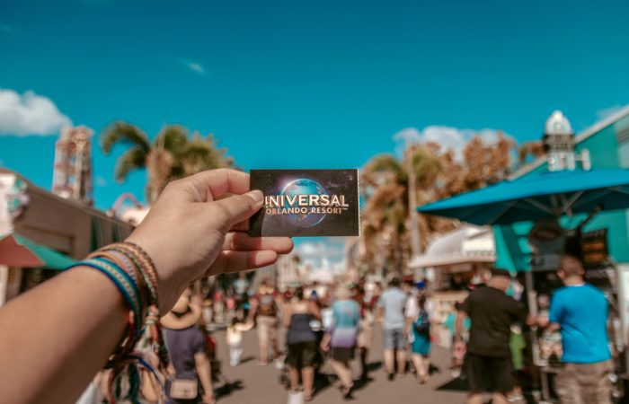 a photo of someone's arm holding out a card for Universal Studios Resort in Orlando with the background being at the theme park.