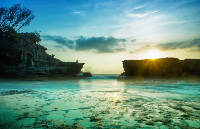 a photo of the beautiful pristine blue ocean water in Bali with the sun setting in the distance