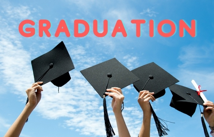 """four graduation caps being held up with the sky as the backdrop with the word """"GRADUATION"""" in pink bold lettering"""